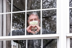 Man wearing mask making heart symbol with hands at the window