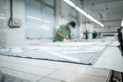 Man wearing medical mask with cutter machine and personal protective equipment at garment industrial work place. Fabric cutter in AsianTextile cloth factory working process tailoring workers equipment