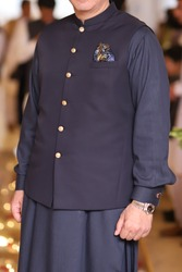 man wearing Pakistani traditional dress shalwar kameez and waist coat with golden buttons and pocket square