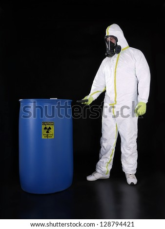 Man wearing protective suit checking radioactivity level of radioactive substance stored in blue container - stock photo