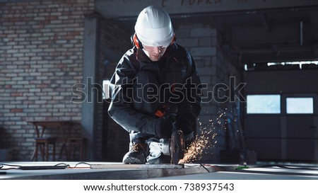 Man wearing protective suit using angle grinder to cut construction materials