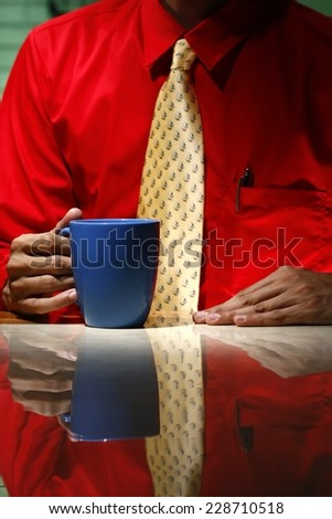 Man wearing red long sleeve shirt, yellow necktie and holding a coffee mug Photo of a man wearing red long sleeve polo shirt and holding his yellow necktie and holding a coffee mug.