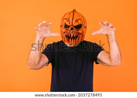 Man wearing scary pumpkin latex mask with blue t-shirt scares with his hands, on orange background. Halloween and days of the dead concept. Сток-фото ©
