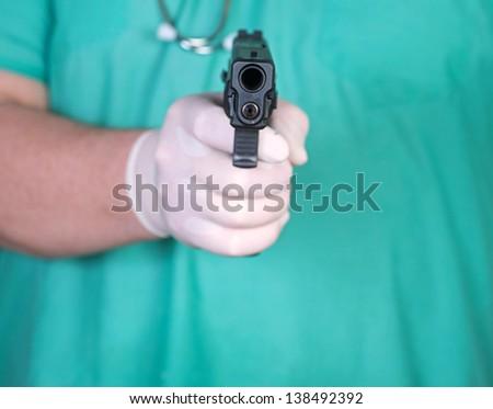 Man wearing surgical scrub shirt, stethoscope & Latex glove pointing handgun straight ahead