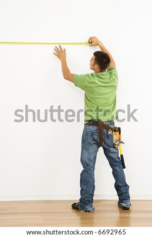 Man wearing tool belt measuring interior wall. - stock photo