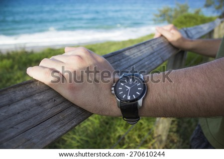 Man wearing watch waits by the beach