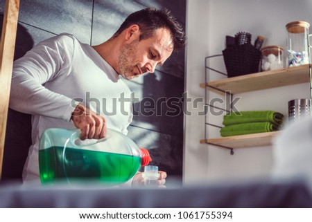 Man wearing white shirt pouring liquid laundry detergent In the bottle cap at laundry room #1061755394