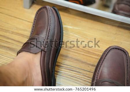 Man wears a classic leather shoe in shoe store, closeup shot #765201496