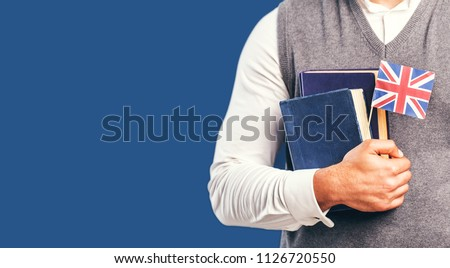Man wears grey sweater vest holds english books and flag before dark blue studio background, language learning concept Foto stock ©