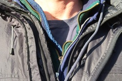 Man wears many layers of clothing with zippers. Layering your clothes is a great strategy for rapidly changing weather, like Colorado in the spring