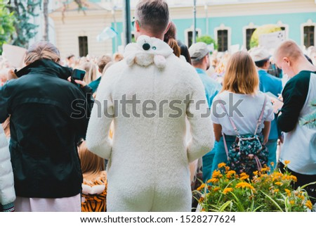 Man wears white bear costume in crowd. Back of male in a costume. Be yourself concept. Wearing pajamas in the city