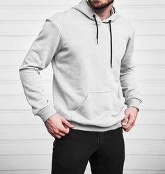 Man wears white hoodie. Bearded young sporty guy is standing in light fleece long sleeve sweatshirt