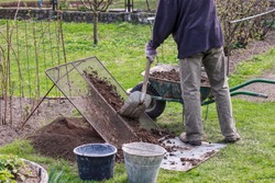 Man wears work outfit. Gardener prepare earth for new flowers and trees. He sifting soil through handmade sieve for better consistency earth and without stones. Plastic black bucket for stones