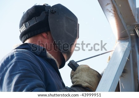Man welder working welding with electrode outdoors