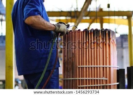 Man welding an industrial equipment in an equipment factory