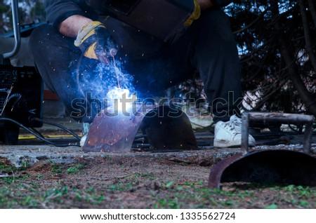 Man welding rusty part of metal and repairing metal structure.Flame glowing of welding steel.Weld metalwork outdoor