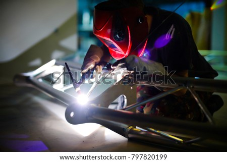Man welds aluminum using tig handle.