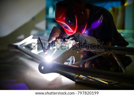 Man welds aluminum using tig handle.