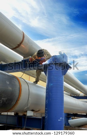 man welds of pipes