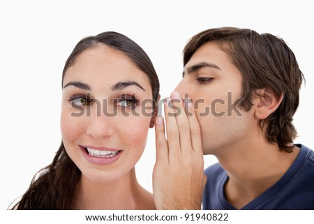 Man whispering something to his fiance against a white background