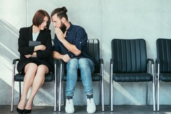 man whispering to a womans ear. office gossip and secrets. colleagues in business workspace.