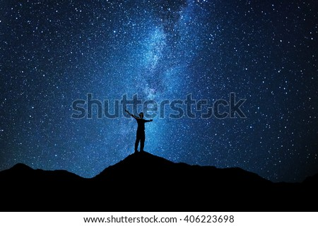 Man who feels on top of the world looking at the milky way #406223698