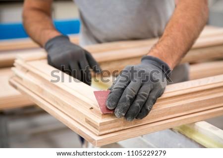 Man who is sanding a window frame