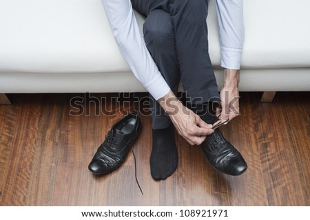 man who ties his black shoes
