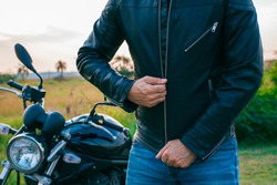 Man whose face is not visible, dressed in jeans and a black jacket, zipping his jacket with a motorcycle behind him on the street.