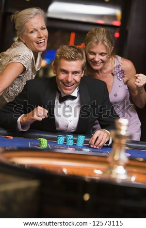 Man winning at roulette table in casino surrounded by glamorous women