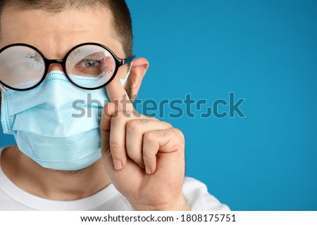 Man wiping foggy glasses caused by wearing disposable mask on blue background, space for text. Protective measure during coronavirus pandemic