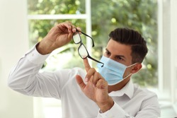 Man wiping foggy glasses caused by wearing medical mask indoors