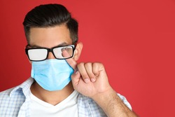 Man wiping foggy glasses caused by wearing medical mask on red background. Space for text
