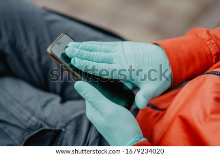 Man wiping the screen of a mobile phone with a gloved hand