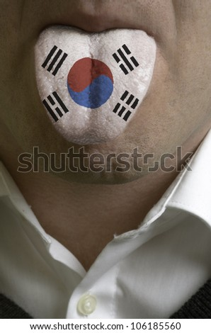 man wit open mouth spreading tongue colored in south korea flag as symbol of values like teaching, learning, multilingual speaking of different languages