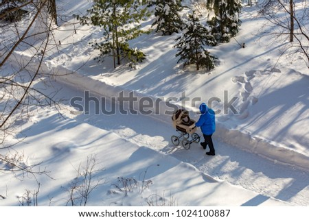 Man with a baby stroller walks through the winter park in the frost #1024100887