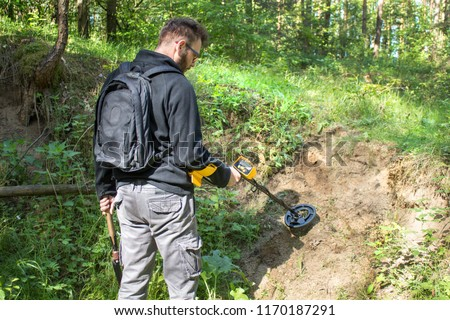 Man with a backpack on his back stands in the forest with a metal detector in his hand and searches the area in search of treasure. #1170187291