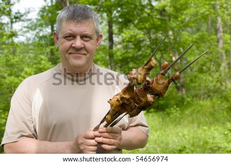 Man with a barbecue chicken. Focus on the barbecue.