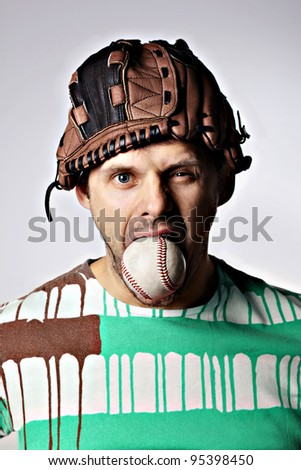 Man with a baseball in mouth and a glove on his head