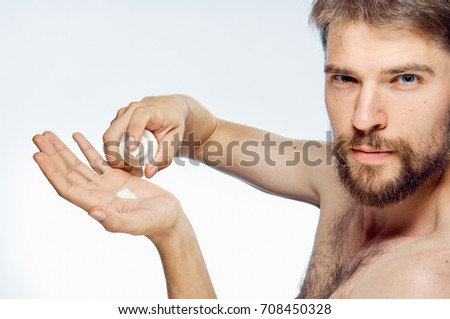 man with a beard looks into the camera and squeezes out the face care cream on the hand on a light background portrait