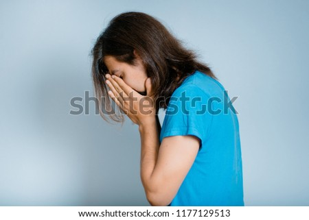 man with a beard sad in depression crying, isolated studio photo on a background