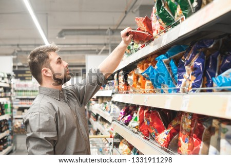 Man with a beard takes a pack of chips from the store shelves. Buyer wears a shirt and buys a snack at a supermarket. Buy a snack for beer.