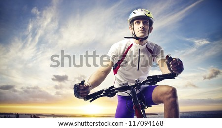 Man with a bicycle on a sunset