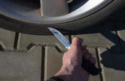 man with a big hunting knife in the parking lot is about to stab, cut the tire. revenge to a neighbor, her mistress's husband, for poor parking at the entrance, envy of a nice car, terrorist attack