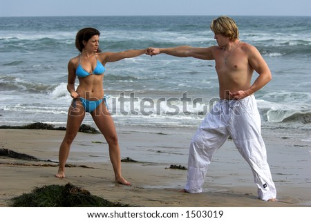 Man with a black belt teaching a woman martial arts on the beach