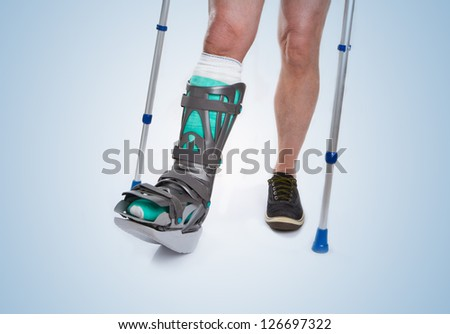 Man with a broken leg with Crutches and Orthotic on a blue background