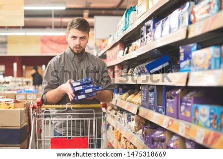 Man with a bundle of cookies in the hands and shopping cart in a supermarket is the department of sweets, looking into the camera. Buyer with a bundle his hands makes purchases in a supermarket.