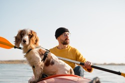 Man with a dog in a canoe on the lake. Young male person with spaniel in a kayak row boat, active free time with pets, companionship, adventure dogs