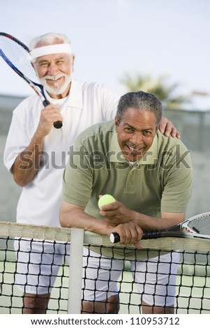 Man with a friend playing tennis - stock photo