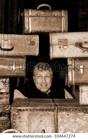 Man with a frightened look on his face in the middle of antique suitcases in sepia tone.